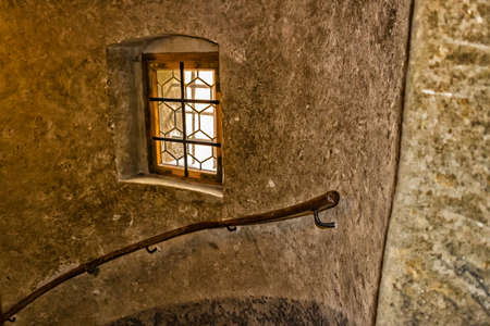 wooden stairs: Medieval window with wooden frame and iron grating in Prague. Ancient stone walls, wooden handrail on large stairs