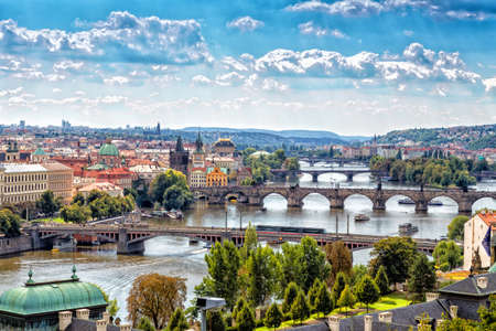 Scenic view of bridges on the Vltava river and of the historical center of Prague: buildings and landmarks of old town with red rooftops and multi-coloured walls.