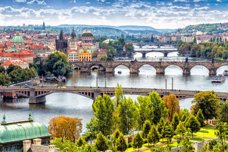 green river: Scenic view of bridges on the Vltava river and of the historical center of Prague: buildings and landmarks of old town with red rooftops and multi-coloured walls.
