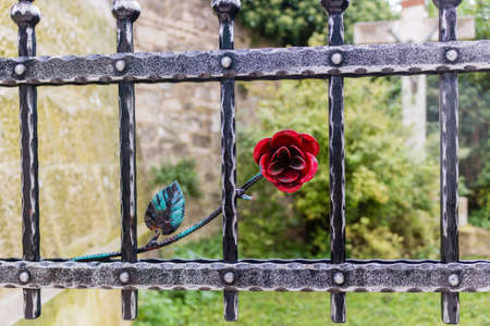 jesus rose: Black and dark grey iron gate with red rose decoration. Wall and green garden on the background with giant crucifix with statue of Jesus Christ Stock Photo