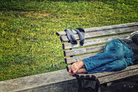 mendicant: Bare feet of a man sleeping on a bench in the city park of Prague