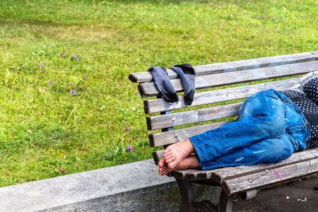 Bare feet of a man sleeping on a bench in the city park of Prague