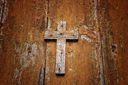 A brownish wooden Catholic cross nailed on grungy orange old wall