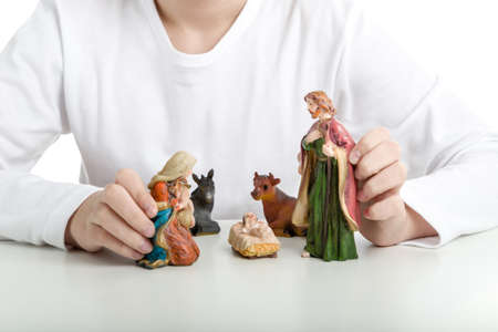 infant jesus: A boy makes a simple Christmas Crib where the little statues represent the Holy Family: the Virgin Mary, Saint Joseph and the infant Jesus, watched by ox and donkey Stock Photo