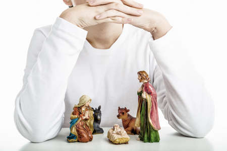 presepio: A boy put his hands as roofs and his arms as walls of the hut of a simple Christmas Crib where the little statues represent the Holy Family: the Virgin Mary, Saint Joseph and the infant Jesus, watched by ox and donkey