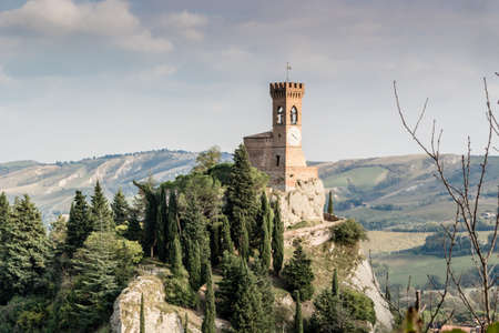 crenellated: The medieval clock tower surrounded by cypress and other trees, viewed from the Rock of Brisighella in Emilia Romagna, Italy.