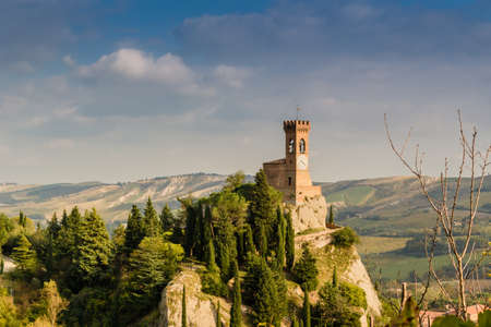 crenellated tower: The medieval clock tower surrounded by cypress and other trees, viewed from the Rock of Brisighella in Emilia Romagna, Italy.