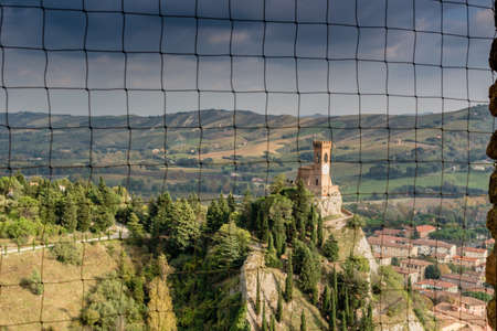crenellated: The medieval clock tower surrounded by cypress and other trees, viewed through the net of th brickwall window of the Rock of Brisighella in Emilia Romagna, Italy.