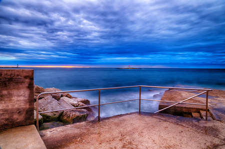 lookout: Sunset on breakwater with stairs on the Mediterranean sea with red steel lookout and green top white lighthouse in the cloudy background near Porec in Croatia