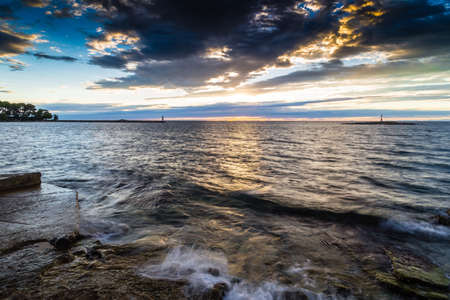 bulkhead: Sunset on prefabricated breakwater on the Mediterranean sea with with red steel lookout lighthouse on small island  green top white lighthouse in the cloudy background near Porec in Croatia Stock Photo