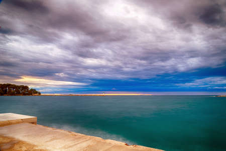 Sunset on prefabricated breakwater on the Mediterranean sea with green top white lighthouse in the cloudy background near Porec in Croatia Stock Photo