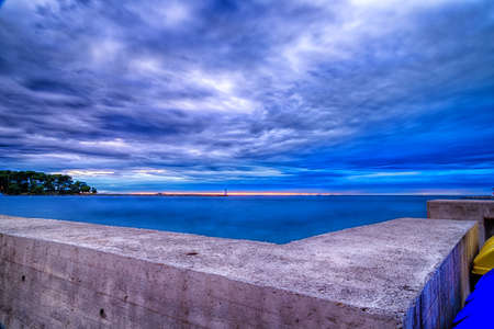 bulkhead: Sunset on prefabricated breakwater on the Mediterranean sea with green top white lighthouse in the cloudy background near Porec in Croatia Stock Photo