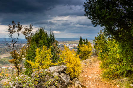 pilgrim journey: Autumn View of the Krizevac (Cross) Mountain in Medjugorje in Bosnia ed Erzegovina: brownish trees, green weeds, orange and yellow leaves and grey rocks Stock Photo