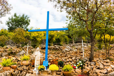 apparition: The Blue Cross and Statue of Blessed Virgin Mary at Apparition Mountain in Medjugorje among grey rocks and green trees and weeds Stock Photo