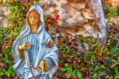 virgin: Statue of the Blessed Virgin Mary with wooden prayer beads necklace in a house rock  garden  with treesin  Medjugorje