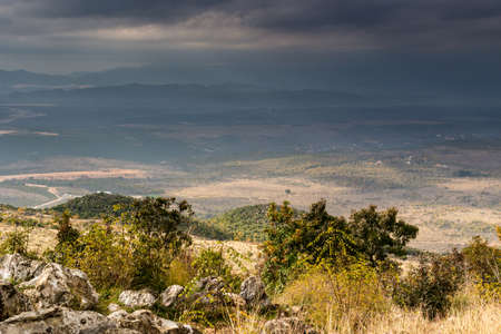 pilgrim journey: Views of the Krizevac Mountain in Medjugorje in Bosnia ed Erzegovina: brownish trees, green weeds, orange and grey rocks Stock Photo