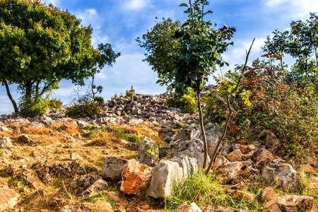 pilgrim journey: Views of the Krizevac Mountain in Medjugorje in Bosnia ed Erzegovina: brownish trees, green weeds, orange, grey rocks and a wooden Cross