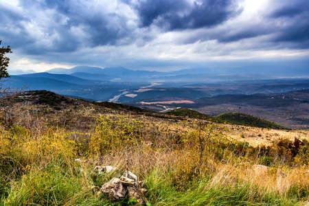 pilgrim journey: Views of the Krizevac Mountain in Medjugorje in Bosnia ed Erzegovina: brownish trees, green weeds, orange and grey rocks Stock Photo