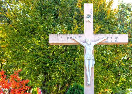 apparition: The large wooden White Cross with crucified Jesus Christ statue  at Apparition Mountain in Medugorje among green trees and weeds