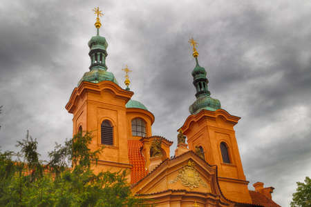 lawrence: Cathedral of St. Lawrence on Petrin Hill in Prague: brown walls and green roofs Stock Photo