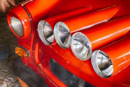 car lots: Four lights of subcompact old red car with lots of lights