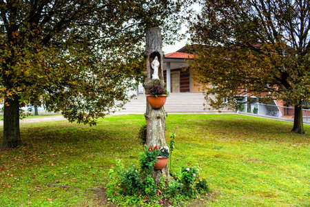 hollow wall: Statue of the Our Lady in hollow trunk the garden in front of the church dedicated to the Blessed Virgin Mary in the village of  Santa Maria in Fabriago near Ravenna in the countryside of Emilia Romagna in Northern Italy.
