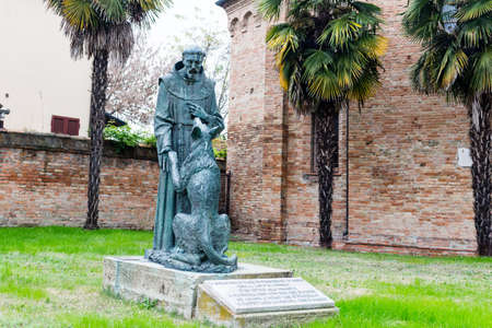 xv century: Saint Francis and the wolf statue in front of the XV century gothic roman church dedicated to Saint Francis in Cotignola near Ravenna in the countryside of Emilia Romagna in Italy.