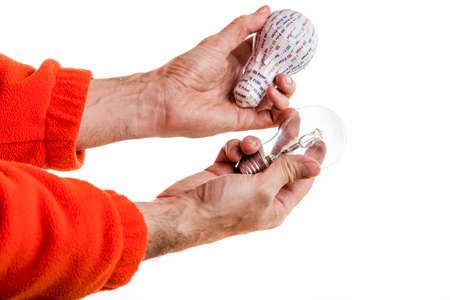 prototypes: Senior hands holding and comparing a 3d print prototype lightbulb and a real glass lightbulb Stock Photo