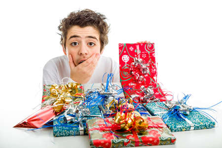 agape: An amazed boy agape holds his chin  with right hand while receiving several Christmas gifts in funny packages and colorful ribbons