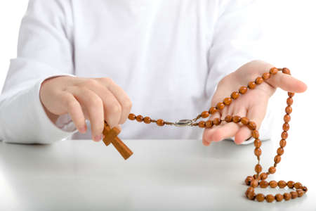 long sleeved: An Italian boy holds Rosary beads with both hands. He wears long sleeved shirt