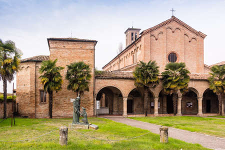 Brickwall facade and colonnade with archs of the XV century roman gothic church dedicated to Saint Francis in Cotignola near Ravenna in the countryside of Emilia Romagna in Italy. Rows of Palm trees and stone bollards border garden.