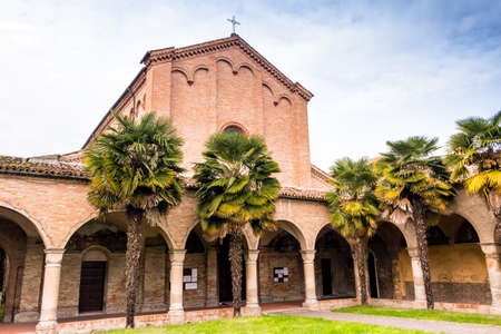 xv century: Brickwall facade and colonnade with archs of the XV century roman gothic church dedicated to Saint Francis in Cotignola near Ravenna in the countryside of Emilia Romagna in Italy. Rows of Palm trees border the garden.