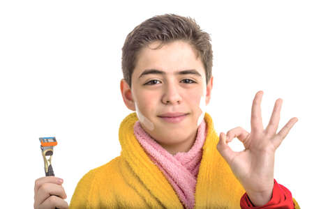all smiles: A Caucasian boy wears a yellow bathrobe with a pink towel around neck: he has patches on his face but smiling makes OK sign whil holding the razor used for shaving