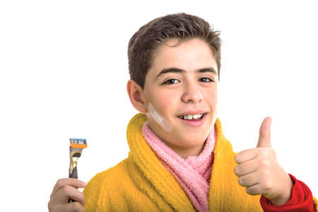 red bathrobe: A Hispanic boy wears a yellow bathrobe with a pink towel around his neck: he has some patches on his face and smiling makes success sign while holding the razor used for shaving