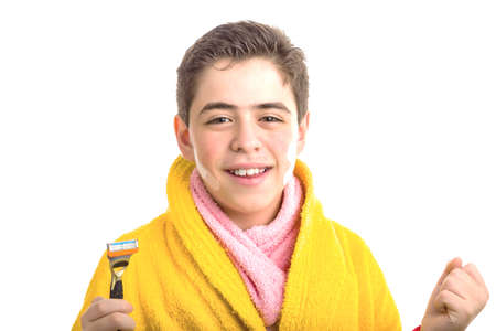 A Hispanic boy wears a yellow bathrobe with a pink towel around his neck: he has patches on his face but he smiles holding the razor he used for shaving photo