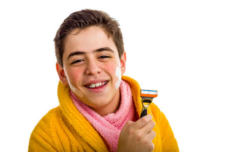 A Hispanic boy wears a yellow bathrobe with a pink towel around his neck: he has some patches on his face but smiles holding the razor he used for shaving photo