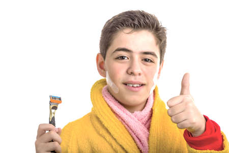 red bathrobe: A Caucasian boy wears a yellow bathrobe with a pink towel around neck: he has patches on his face but smiling makes success sign with thumb while holding the razor used for shaving Stock Photo