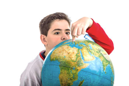 eyes hidden: A Caucasian boy hidden behind a globe reveals only the eyes and part of the face while pointing the map with index finger Stock Photo