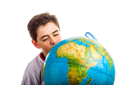 eyes hidden: A Caucasian boy hidden behind a globe reveals only the closed eyes and part of the face Stock Photo