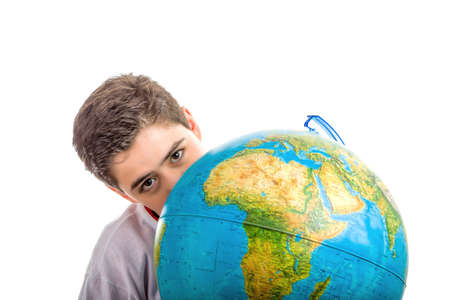 eyes hidden: A Caucasian boy hidden behind a globe reveals only the eyes and part of the face