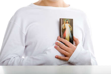 merciful: A Caucasian boy holds resting on his chest a picture of Merciful Jesus Stock Photo