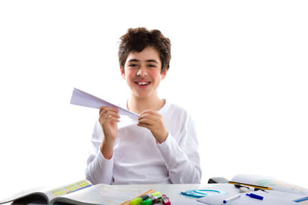 shaping: A caucasian boy is playing with a paper airplane sitting in front of homework. He is holding it with the right hand while the left hand is shaping the tip