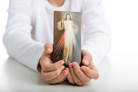 the merciful: A Caucasian boy shows a picture of Merciful Jesus  holding it with both hands