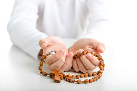 Young hands offer brown wooden rosary beads with open palms upward
