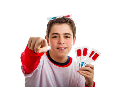 A Caucasian boy wears a pair of 3D Cinema paper eyeglasses on his head with red and sky-blue lenses and holds other 4 ones with left hand pointing index finger to viewer with right hand Stock Photo