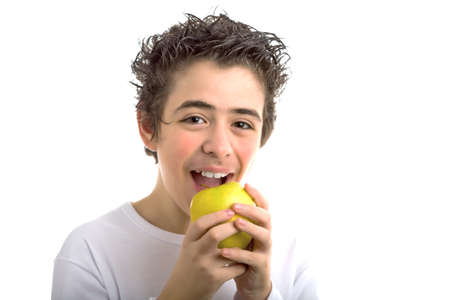 sleeved: A handsome Caucasian boy wearing a long sleeved white shirt is goingt to bite and eat a yellow apple with both hands