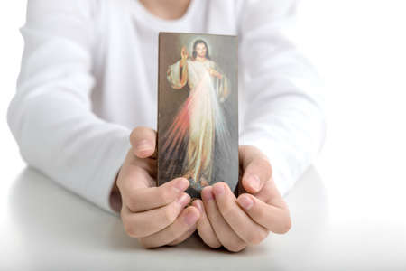 the merciful: A Hispanic boy shows a picture of Merciful Jesus  holding it with both hands