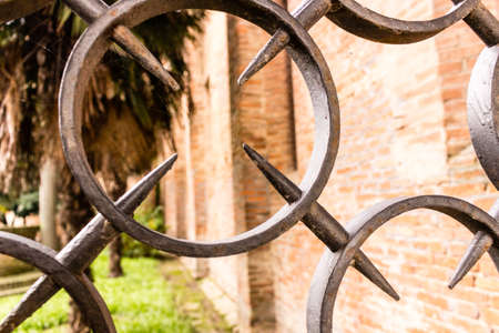xv century: View through the rounds and spikes of an iron grate of the brickwall cloister of the XV century roman gothic church dedicated to Saint Francis in Cotignola in Italy