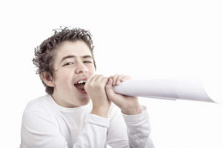 medium length: Handsome smiling  hispanic boy with medium length hair and questioning eyes shouts in a fake megaphone made with white paper Stock Photo