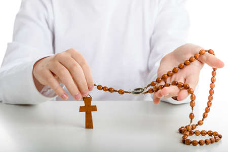 merciful: A Caucasian boy with both hands holds Rosary beads with icon of Merciful Jesus among grains Stock Photo